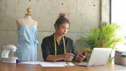 Asian freelance designer using smart phone, business lifestyle.