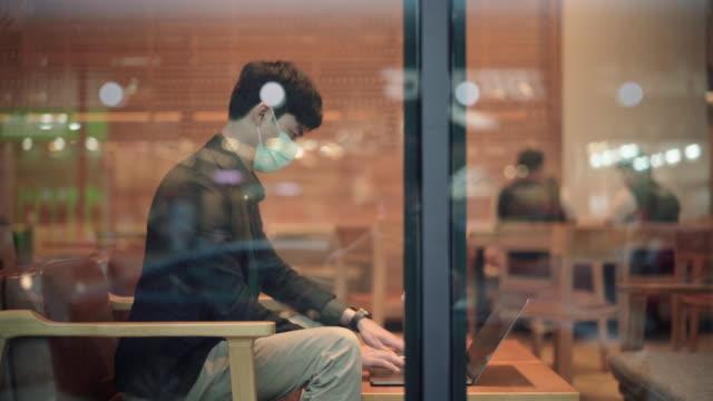 vidéos et rushes de homme indépendant asiatique utilisant le masque de pollution pour employer l'ordinateur portatif au café - asie du sud est