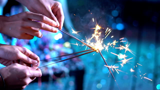 asian friends holding lit sparklers at dinner party - sparkler stock videos & royalty-free footage