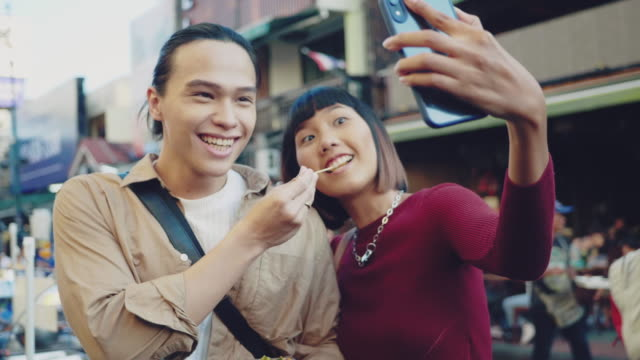 asian friends take a photo of thailand street food at khao san road. - mercato delle pulci video stock e b–roll