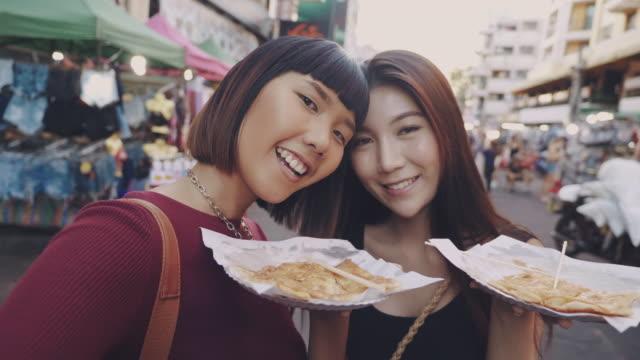 asiatiska vänner ta ett foto av thailand street food på khao san road. - thailändskt ursprung bildbanksvideor och videomaterial från bakom kulisserna