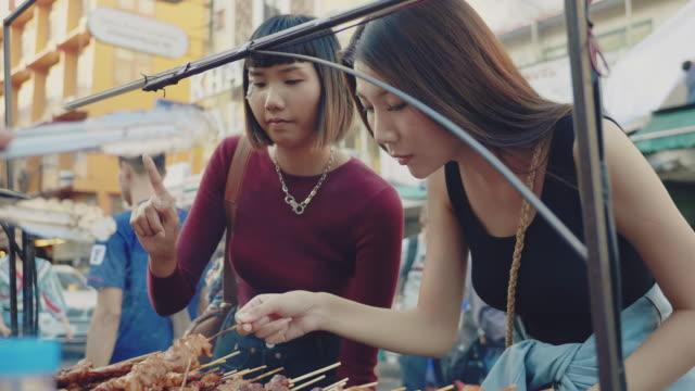 asiatische freunde touristen wählen bbq mit ihrem freund auf dem flohmarkt. - marktstand stock-videos und b-roll-filmmaterial