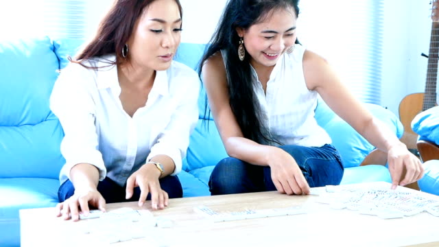 Asian friendship smilling and playing domino game on sofa