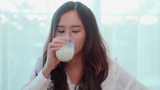 カジュアルなドレスを着たアジアの女の子20〜30歳は、朝食を食べてミルクを飲んでいます。あなたが仕事を離れる前の朝に。 - 盛り付け点の映像素材/bロール