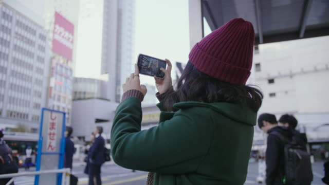 asian girl admiring the city and taking pictures or video on smart phone while waiting for transport at bus stop. - photography stock videos & royalty-free footage