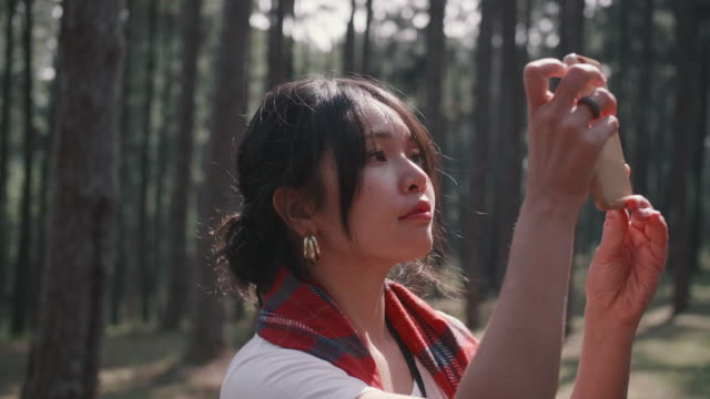 asian girl admiring the view on a beautiful sunny day and taking photos with smartphone - photographer stock videos and b-roll footage