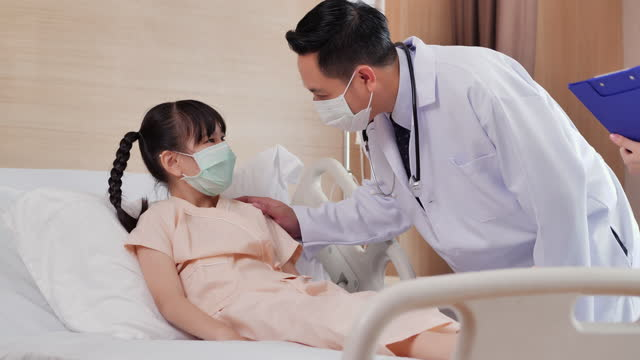 asian girl age 9 yearold lying on the bed with protective face mask and talking to male nurse doctor visits her and pediatrician touching of shoulder at hospital.doctor and patient consultation concept. - pediatrician stock videos & royalty-free footage
