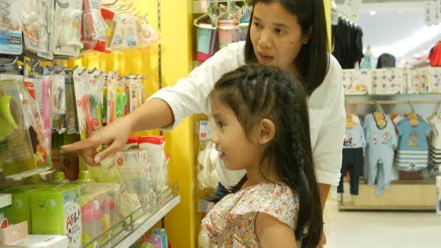 Asiatisk tjej och mamma ha kul shopping tillsammans