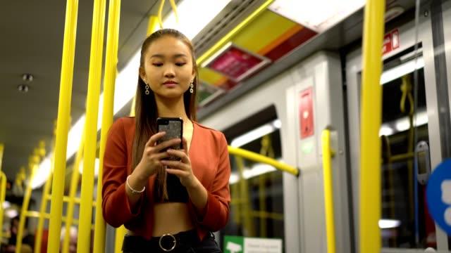 vidéos et rushes de fille asiatique bavardant en ligne dans un train - une seule adolescente