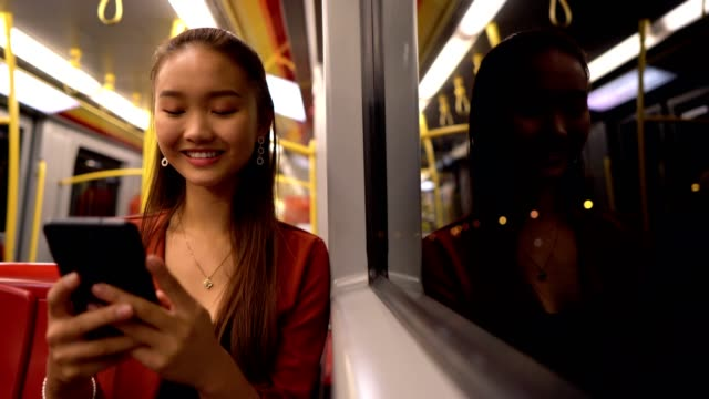 asian girl chatting online in a train - subway train stock videos & royalty-free footage