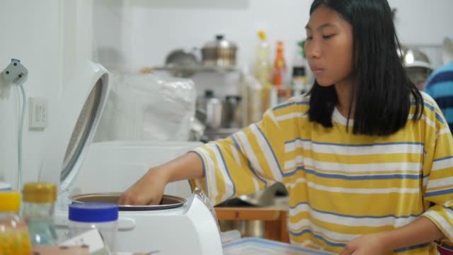 アジアの女の子は自宅で台所で米を調理し、女の子は彼女の母親が食べ物を準備するのを助けます。 - 容器点の映像素材/bロール