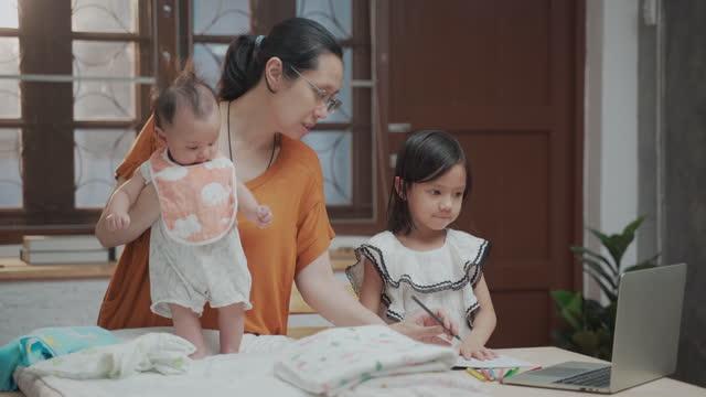 vídeos de stock, filmes e b-roll de menina asiática fazendo lição de casa com sua mãe e irmã em casa - vista frontal