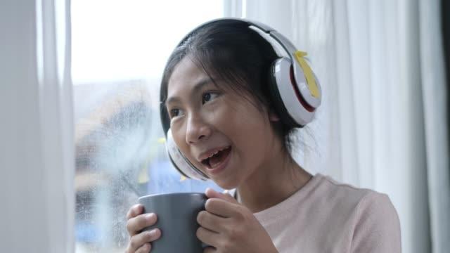 vídeos de stock, filmes e b-roll de garota asiática bebendo bebida quente e ouvindo música perto da janela em casa, conceito de estilo de vida. - homem e máquina