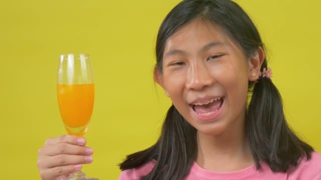 asian girl drinking orange juice with yellow background. - ascorbic acid stock videos & royalty-free footage