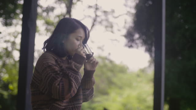 asian girl drinking some hot coffee on balcony with view the nature. - veranda stock videos & royalty-free footage