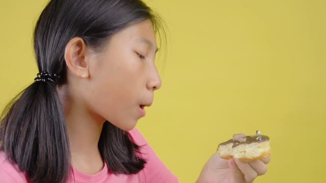 vídeos de stock e filmes b-roll de asian girl eating chocolate donut on yellow background slow motion - mastigar