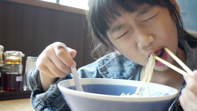 Asian girl eating delicious noodles with chopstick
