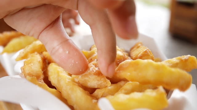asian girl eating french fries, slow motion - chips stock videos & royalty-free footage