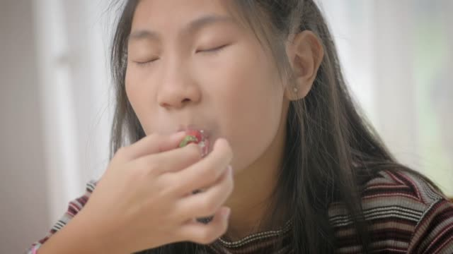 asian girl eating fruit cake with sweet and sour taste, slow motion. - sour taste stock videos & royalty-free footage