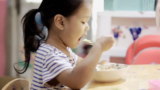 vídeos de stock e filmes b-roll de asian girl eating noodle - bebés meninas