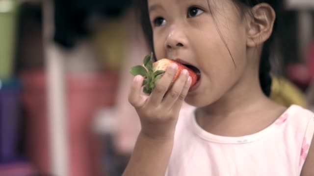 asian girl eating strawberry - raw food diet stock videos & royalty-free footage