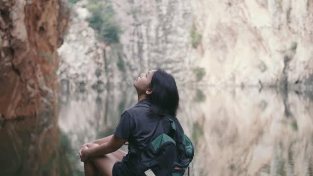 アジアの女の子は、リヴの横でリラクゼーションを楽しんでします。 - 景勝地点の映像素材/bロール