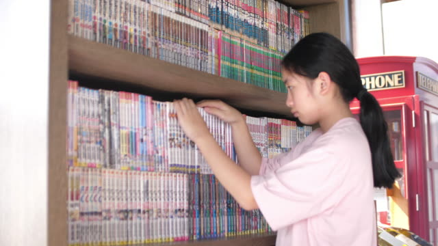 asian girl finding a book in the library, 4k - book shop stock videos & royalty-free footage