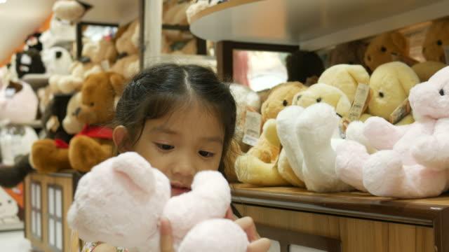 stockvideo's en b-roll-footage met aziatisch meisje met plezier winkelen speelgoed - speelgoed