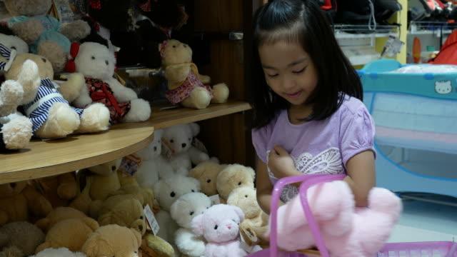 asian girl having fun shopping toy - teddy bear stock videos & royalty-free footage
