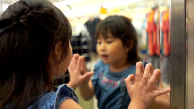 vídeos de stock e filmes b-roll de asian girl having fun to fitting cloth in front of mirror - viciado em compras