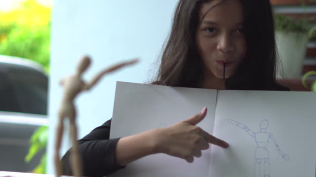 asian girl holding her drawn human figure on paper and showing thumbs up sign - one girl only stock videos & royalty-free footage