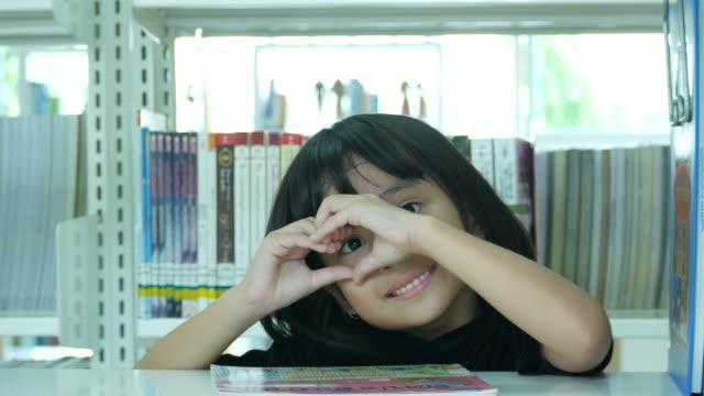 asiatin in bibliothek, herzschild - welcome schild stock-videos und b-roll-filmmaterial