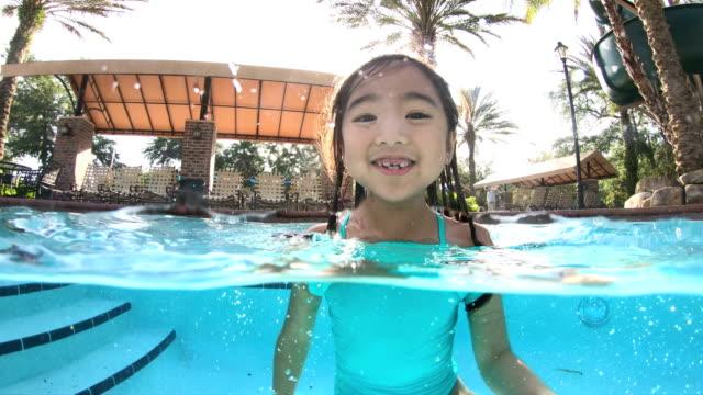 asian girl in swimming pool jumping - florida stati uniti video stock e b–roll