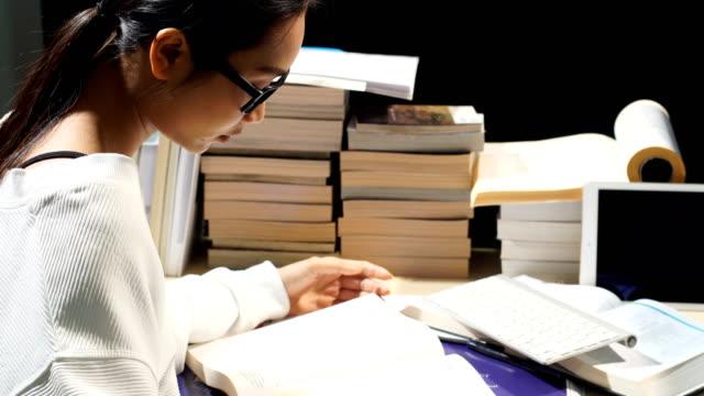 vídeos de stock, filmes e b-roll de menina asiática na camisa branca, lendo muitos livros sobre a mesa com muitos alto empilhamento de livro - grupo grande de objetos