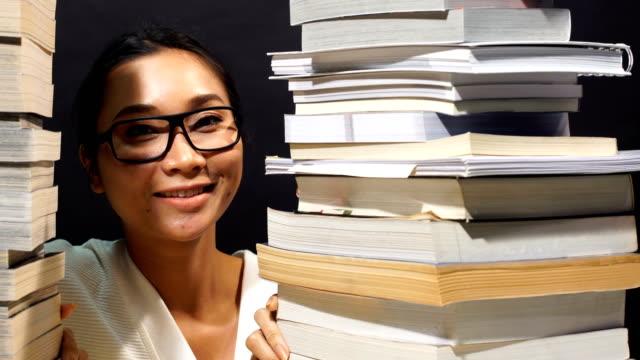 asiatische mädchen in weißen hemd viele lehrbücher auf tisch mit vielen hohen stapeln von buch lesen - viele gegenstände stock-videos und b-roll-filmmaterial