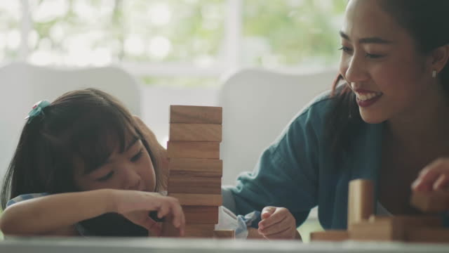 Asian girl is playing wooden block toy beside her teacher for supporting in classroom