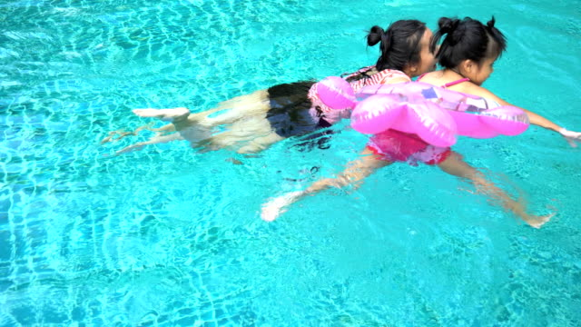 Asian girl Is swimming with her mother