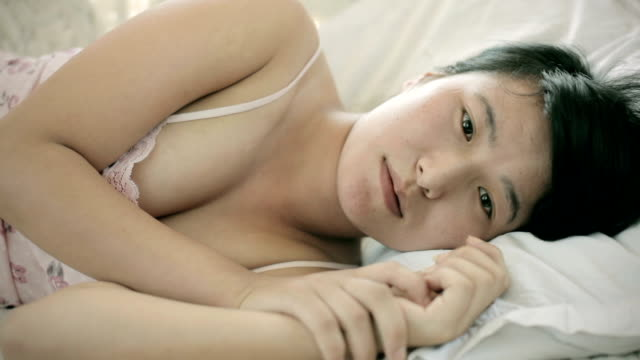 Asian girl laying on sofa and thinking with blank expression.