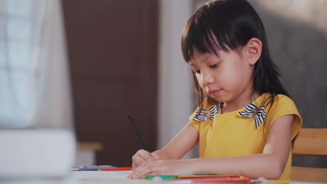 vídeos de stock, filmes e b-roll de garota asiática aprende e desenha enquanto senta na sala de estar em casa - desenhar atividade