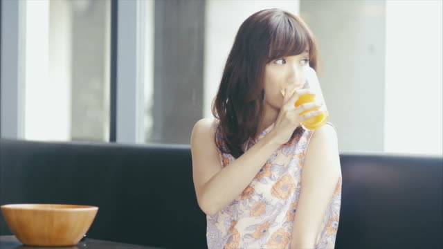 アジアの女の子を覗きながら、窓とジュース - グラス点の映像素材/bロール
