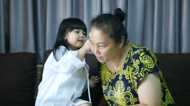 Asian girl playing doctor and patient with grandmother