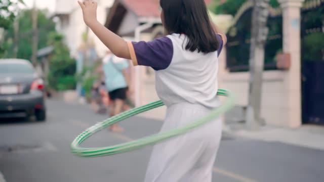 asian girl playing hula hoop outdoor - plastic hoop stock videos & royalty-free footage