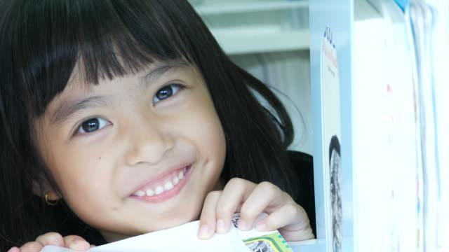 vídeos de stock, filmes e b-roll de menina asiática jogando na biblioteca - sabedoria