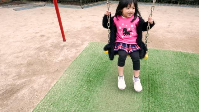 asian girl playing in the park - ブランコ点の映像素材/bロール