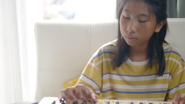 vidéos et rushes de fille asiatique jouant l'instrument de clavier près de la fenêtre à la maison, concept de mode de vie. - doigt humain