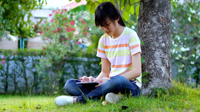 asian girl playing tablet under tree in public park