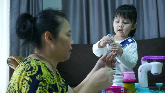 Asian girl playing trade ice cream with grandmother