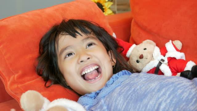 Asiatin mit Santa Puppe auf roten Sofa spielt