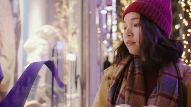 asian girl putting on a woollen hat & scarf . she shopping at christmas market in city. - window display stock videos & royalty-free footage
