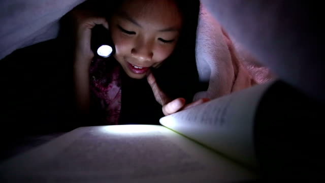 Asian girl reading a book in bed with flashlight